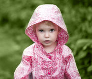Cute little girl in the rain. A cute little girl in the rain, dressed in a pink raincoat Royalty Free Stock Photos