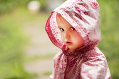 Cute little girl in the rain. A cute little girl in the rain, dressed in a pink raincoat Stock Image