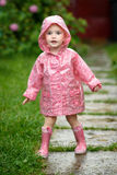 Cute little girl in the rain. A cute little girl in the rain, dressed in a pink raincoat and pink boots Stock Photography