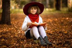 Cute little girl read interesting book in autumn. Park stock images