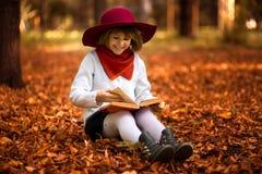 Cute little girl read interesting book in autumn. Park stock photos
