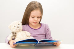 Cute little girl reading a book. Cute little girl is reading a book and a bear Stock Photo