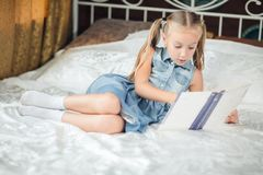 Cute little girl in denim sundress reading book on bed at home royalty free stock photos