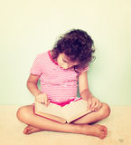 Cute little girl reading a book. filtered image Stock Images