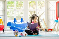 Cute little girl is reading a book . Funny kid having fun in kid royalty free stock image