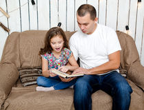 Cute little girl is reading the book with her father on the sofa Royalty Free Stock Image