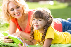 Cute little girl reading book with her mother and Royalty Free Stock Photo