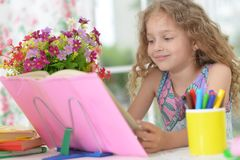 Little girl reading book. Cute little girl reading book at home stock images