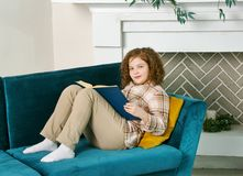 Little girl reading book at home. Cute little girl reading book at home on the couch stock photography