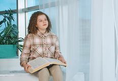 Little girl reading book at home. Cute little girl reading book at home royalty free stock photography