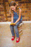 Cute little girl reading book in library Royalty Free Stock Photo