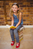 Cute little girl reading book in library Stock Photos