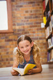 Cute little girl reading book in library Royalty Free Stock Photos