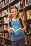 Cute little girl reading book in library Stock Images