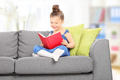 Cute little girl reading a book in the living room stock photo