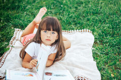 Little beautiful girl lie on grass with book looking at camera. Cute little girl is reading a book while lying on green grass looking to the camera Stock Photography