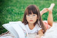 Little beautiful girl lie on grass with book looking at camera. Cute little girl is reading a book while lying on green grass looking to the camera Royalty Free Stock Image
