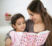 Cute little girl reading book with mother Stock Photos