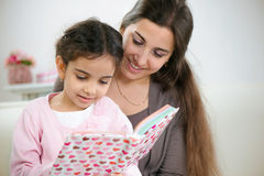 Cute little girl reading book with mother Stock Photo