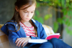 Cute little girl reading a book outdoors Royalty Free Stock Photos