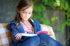 Cute little girl reading a book outdoors Stock Photography