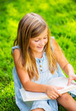 Cute little girl reading book outside on grass. Relaxing outside in backyard Royalty Free Stock Photo