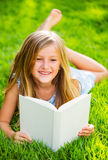 Cute little girl reading book outside on grass. Relaxing outside in backyard cheerful girl Royalty Free Stock Photos