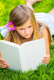 Cute little girl reading book outside on grass. Relaxing outside in backyard contemplating Royalty Free Stock Image