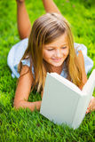 Cute little girl reading book outside on grass. Relaxing outside in backyard interesting book Stock Photography