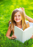 Cute little girl reading book outside on grass Royalty Free Stock Images