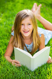 Cute little girl reading book outside on grass. Relaxing outside in backyard smiling Stock Photo