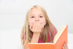 Cute little girl is reading book Royalty Free Stock Photography