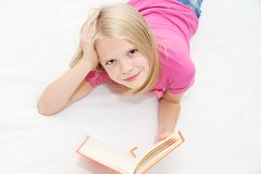 Cute little girl is reading book Stock Photography