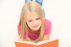 Cute little girl is reading book Stock Images