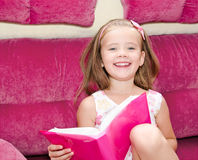 Cute little girl reading a book and siting on the sofa Stock Photography