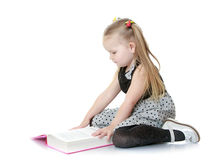 Cute little girl reading a book sitting on the Royalty Free Stock Image