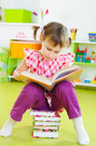 Cute little girl reading book sitting on floor Stock Photos
