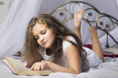 Cute little girl reading a book and smiling while lying on a bed in the room stock photography