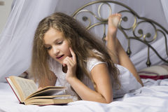 Cute little girl reading a book and smiling while lying on a bed in the room royalty free stock photo