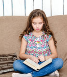 Cute little girl is reading the book on the sofa. At home Stock Photos