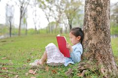Cute little girl reading book in summer park outdoor lean against tree trunk in the summer garden.  stock image