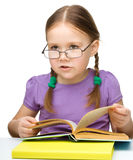 Cute little girl reading book wearing glasses Stock Photos