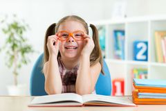 Cute little girl reading a book while wearing Stock Photography