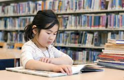 Cute Little Girl Reading Books at Library Stock Photos