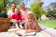 Cute little girl reading lying on the grass Royalty Free Stock Photo