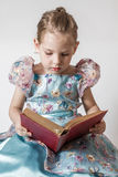 Cute Little Girl Reading an Old Red Stock Photo