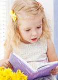 Cute little girl reading stock images