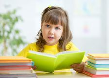 Cute little girl reading story from big book in Royalty Free Stock Photos