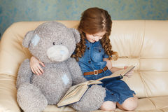 Cute little girl reading with teddy bear Stock Photography