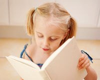 A cute little girl reads a book Royalty Free Stock Images